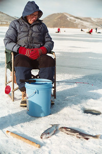 Bundled up, freezing to death and staring at a hole in the ice. Yes, this is ice fishing at its best. Man keeps an eye on his fishing hole in the ice at Scofield Reservoir, Utah