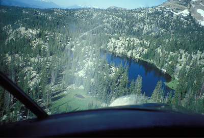 Airplane approaches a high alpine lake to stock fingerling from the air.  This view is from the cockpit of the plane.  Photo by Utah Division of Wildlife Resources taken 7/15/1998.