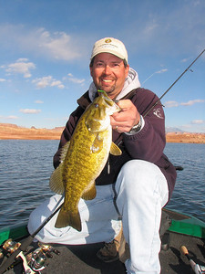 Angler shows off his smallmouth bass caught at Lake Powell on 2-14-07.  By Utah Division of Wildlife Resources.