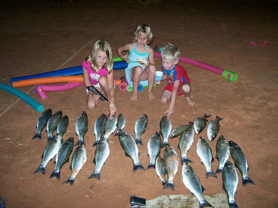 Jamie, Molly and Mikey Packer of Page Arizona with stripers caught from the back of a houseboat in a nearby striper boil.  Photo by Utah Division of Wildlife Resources.