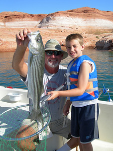 Mitch Blankard (8) and his dad show 4.8 lb striper Mitch caught at Lake Powell near bouy number 3 on 6-24-08.  By Utah Division of Wildlife Resources
