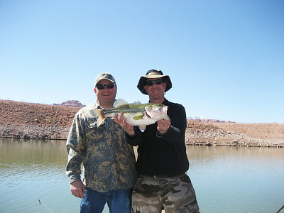Standing by his friend, Brad Kendrick (R) holds his 5-lb. largemouth bass he caught at Lake Powell on 3-14-08.  By Utah Division of Wildlife Resources