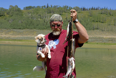Sheldon Davis of Indianola, Utah fishes with dog in arm at Miller Flat Reservoir on 7-4-07.  By Brent Stettler, Utah Division of Wildlife Resources