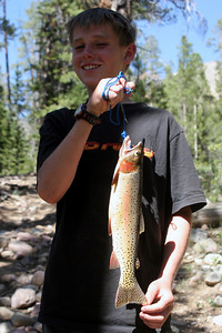 Brayden Swasey of Hooper proudly displays a nice cutthroat trout he caught in a high Uintas stream.  Catching trout is particularly meaningful because his great grandfather stocked fish in the Uintas south slope by hauling in milk cans with fish in them.  Swasey Hole Lake is named after Brayden's grandfather.  Photo taken 6-29-07 by Phil Douglass, Utah Division of Wildlife Resources.