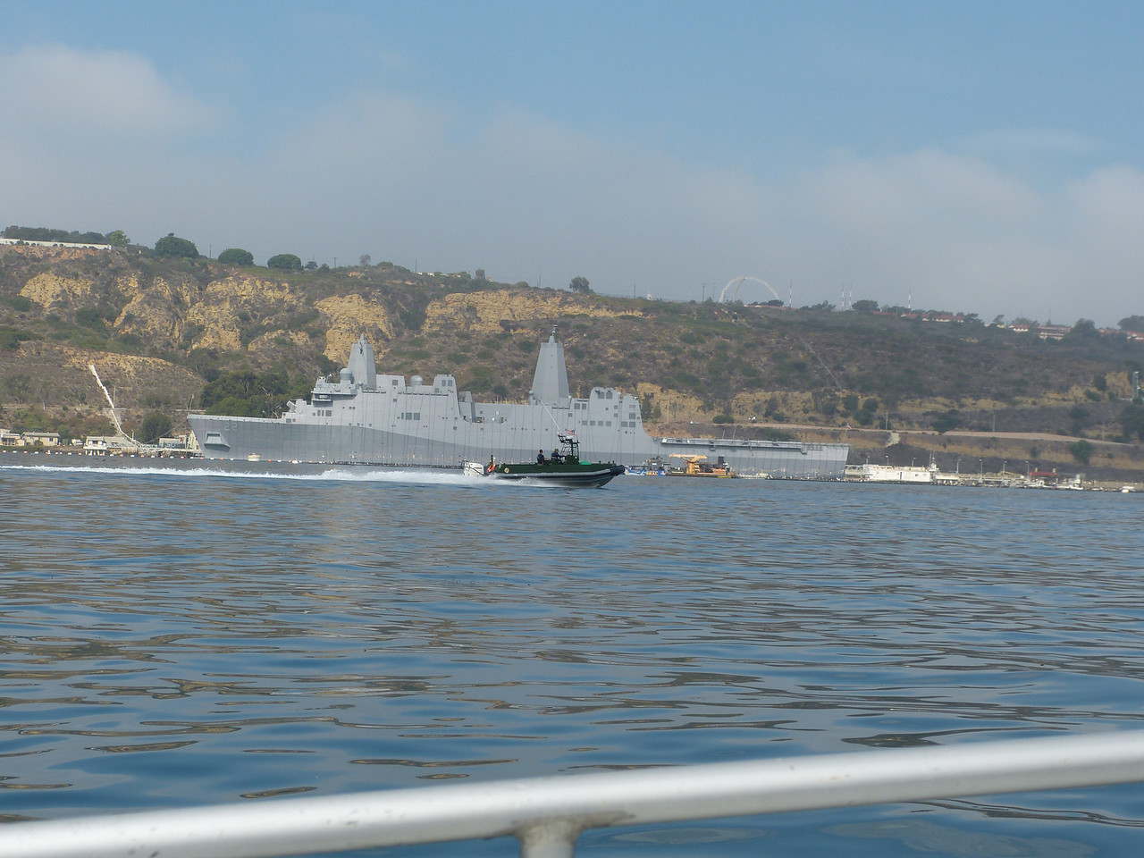 """a Homeland Security vessel speeds along the length of the USS San Diego    (and when I say """"speeds"""", I mean it; Homeland Security boats are driven in the fastest, most reckless manner of any boats I have seen on the water when it wasn't Memorial Day)"""