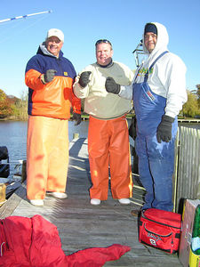 11/17/2005  I fished with Gary Arnold and his clients Jerry and Mark.  What a difference a day makes.  See the fish they are holding?  Right, there are none.  Jerry was high hook however because he had two fish hit his plug but blew them both.  That's OK Jerry, we know you dropped them on purpose so as to not make us look bad.  Lunch was excellent thanks to Mark.  It was cold and windy and the water was all churned up for most of the day.  It made fishing tough.  No bait could be found so we plugged it all day.  I am sure there is still bait in the bay but when they will show and where they are is a mystery as of today.  It was still a good day on the water with a lot of laughs.  Captain Al Lorenzetti