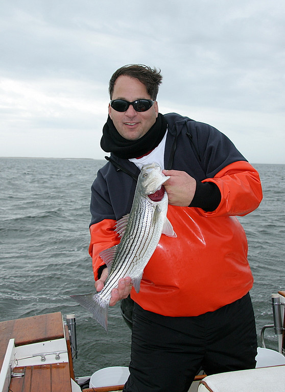 11/16/2006<br /> <br /> I fished with Anthony DeBlasio and Mark Epstein.  We worked hard at plugging and fishing with bait but came up short, literally.  Here is Anthony with one of the fish we caught today.  This little bass hit a big wooden plug about half it's size.  We had a few others but nothing big.  Little fish is a sign of things slowing down.  The weather has been lousy all week and that might have something to do with it.  The water temperature is still warm at 63 degrees.  I think we might still have a shot at some fish but it is all a question mark right now.  Anthony and Mark cast plugs till their arms were weary.  It was a tough day but better than a day at work, at least for them.  For me it was just tough but we did have a good time.  Thanks guys for your patience.<br /> <br /> Captain Al Lorenzetti