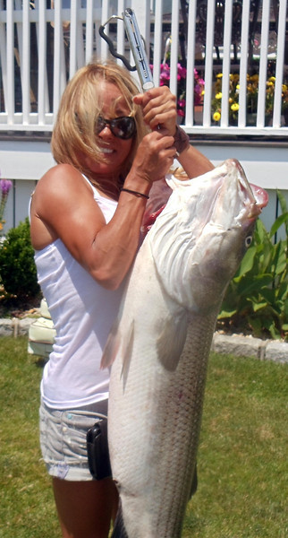 name: boyd riedell<br /> <br /> Date Caught: 7-12-10<br /> <br /> Location: ocean<br /> <br /> Photo Description: got some good fish to east..its been a great season and just sharing some of the fun..my lady holding a 42 pound fish..rest released..this one caught on a bunker head to get past the blues crashing the pods...