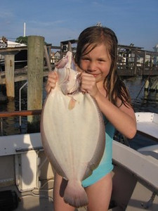6/23/2010<br /> <br /> Julia Lawton catches her first keeper Fluke in Reynolds channel. The Fluke was caught using a bucktail and Gulp combo.