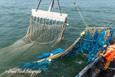 The bag of the net is already beside the ship. / De zak van het net is al naast het schip.