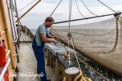 The skipper varies a link. / De schipper wisselt een koppeling.