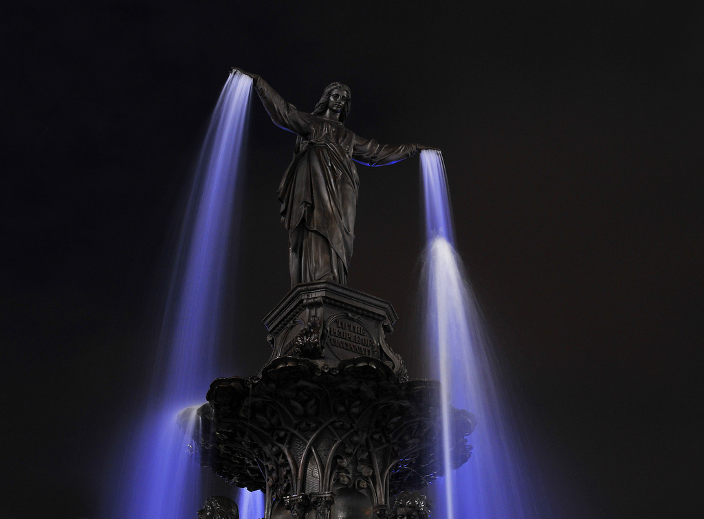 Genius of the Waters Fountain Square Cincinnati Ohio<br /> The Lady tops the beautiful Tyler Davidson fountain It was given to the city by Henry Probasco<br /> All natural light, the blue from the 5/3 neon wall, the white light from the Christmas skating rink.