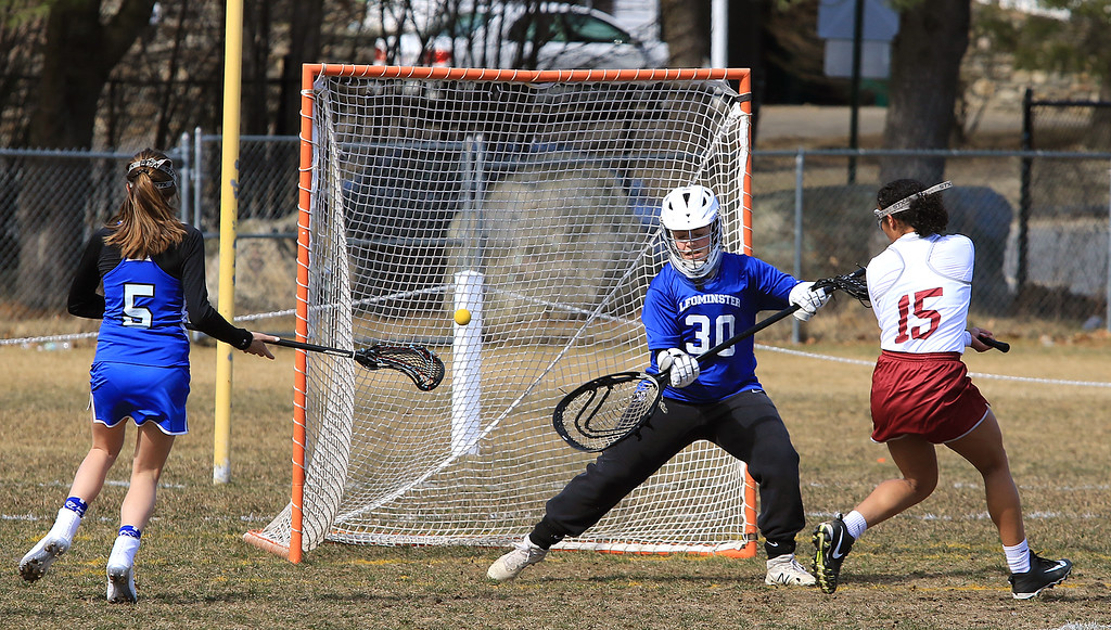 . Leominster High School girls lacrosse visited Fitchburg on Thursday to play Fitchburg High School. FHS\'s Diandra Bodie fires a shot on LHS goal past Alexis Hahn for a point in the first half of the game. SENTINEL & ENTERPRISE/JOHN LOVE