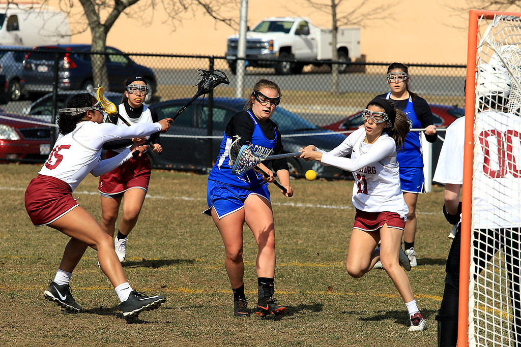 . Leominster High School girls lacrosse visited Fitchburg on Thursday to play Fitchburg High School. FHS\'s MIchelle Tome tries to stop a shot on goal by LHS\'s Lauren Caponi during action in the first half of the game. SENTINEL & ENTERPRISE/JOHN LOVE