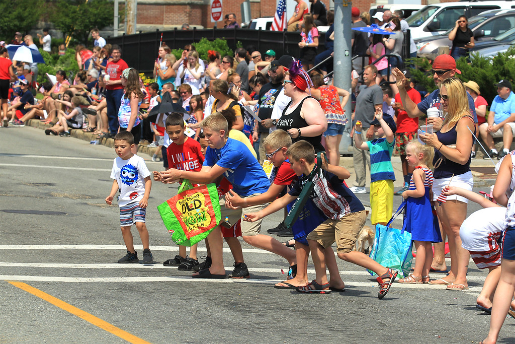 . Kids rush out for the candy being tossed out on the parade route SENTINEL&ENTERPRISE/Scott LaPrade