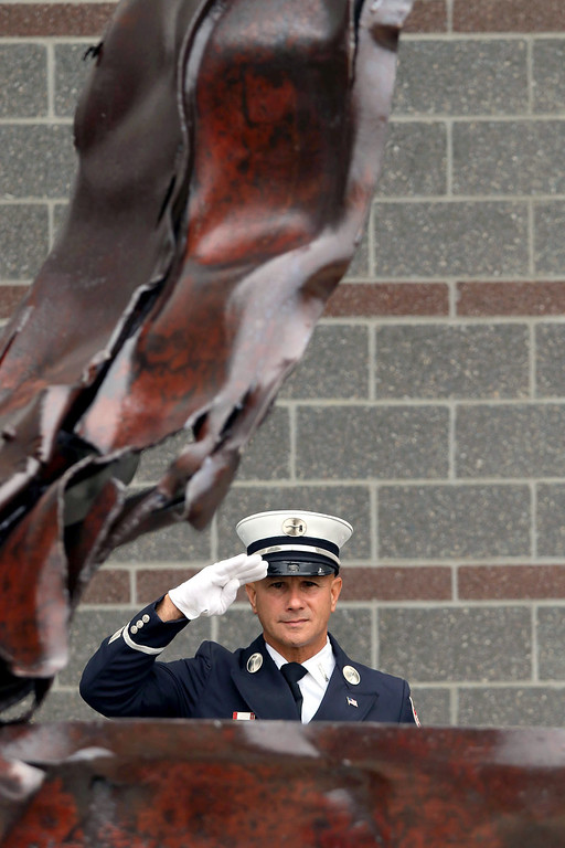 . Fitchburg Fire Lt. Richard Liberatore salutes as he stands behind a piece of the World Trade Center towers, which is now part of a monument that rests out in front of the station on North Street, as the flag is lowered at the 9-11 ceremony on Tuesday, September 11, 2018. SENTINEL & ENTERPRISE/JOHN LOVE