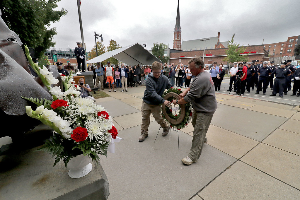 . Phil Esposito owner of Montachusett Contracting Co., Inc. and Montachusett Regional Vocational Technical High School senior Troy Brassard place a wreath at the 9-11 ceremony held at the North Street station house Tuesday, September 11, 2018. SENTINEL & ENTERPRISE/JOHN LOVE