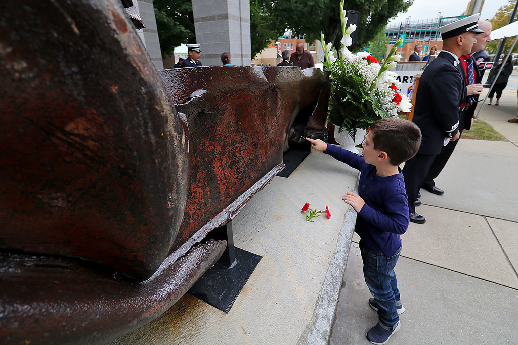 . Fitchburg Fire Lt. P.J. Roy\'s son James gets a close up look at a piece of the World Trade Center towers, which is now part of a monument that rests out in front of the station on North Street, after the  9-11 ceremony on Tuesday, September 11, 2018. SENTINEL & ENTERPRISE/JOHN LOVE