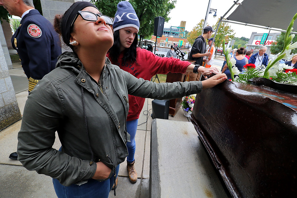 . Montachusett Regional Vocational Technical School masonry students Kiara Vazquez, 17, and Allie Hobby, 17, check out the beam from the World Trade Centers during the 9-11 ceremony at the North Street Fire Station on Tuesday, September 11, 2018. SENTINEL & ENTERPRISE/JOHN LOVE