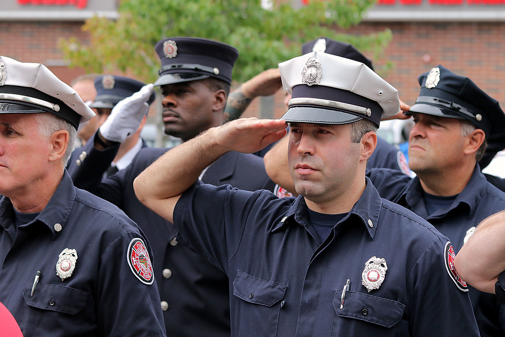 . Fitchburg Fire Lt. Ryan Cringan salutes with his fellow firefighters as the flag is lowered at the 9-11 ceremony held at the North Street station house Tuesday, September 11, 2018. SENTINEL & ENTERPRISE/JOHN LOVE