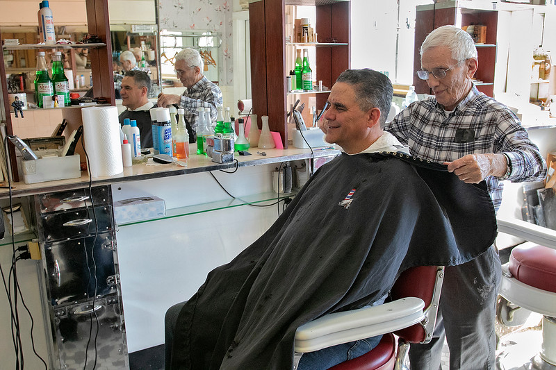 Saturday - Bob Pelullo in his shop Ideal Barbers on Day Street in Fitchburg, March 14, 2020. He has been cutting hair at this shopo since 1961. His father opened it in 1948. He said that he is not that worried about the virus and this is the first time he has seen anything like this. He said that he has not lost any business due to the virus. It is mostly business as usual but he is not really sure how it will effect his business. This is the first time in all his years that he has seen any thing like this. He has bought more hand sanitizer. Veteran David Reyes got his hair cut on Saturday and said he was not to worried about the coronavirus. SENTINEL & ENTERPRISE/JOHN LOVE