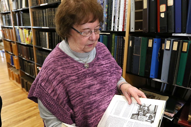 Volunteer at the Fitchburg Historical Society Simone Blake talked about what she does for them at their offices on main Street Friday morning, April 6, 2018 as she shows off one of the book in the their library that has a black and white picture of her helping a girl scout, many years ago. SENTINEL & ENTERPRISE/JOHN LOVE