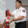 Fitchburg firefighter Phil Jordan talks about how to use a fire extinguisher to the crowd at the fire station on North Street during the City's National Night out on Tuesday. SENTINEL & ENTERPRISE/JOHN LOVE