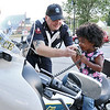 Brooke Bregh, 3, of Fitchburg gets some help from Fitchburg Officer Michael Faucher as she sits on his police motorcycle and tries out the speaker at Fitchburg's National Night Out. She was telling people to pull over. SENTINEL & ENTERPRISE/JOHN LOVE