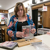 Angela Lopes, working the circulation desk at the Fitchburg Public Library, takes the security covers off some movies as she helps Larry Seggelin of Fitchburg check out the movies he picked on Wednesday, Oct. 9, 2019. SENTINEL & ENTERPRISE/JOHN LOVE