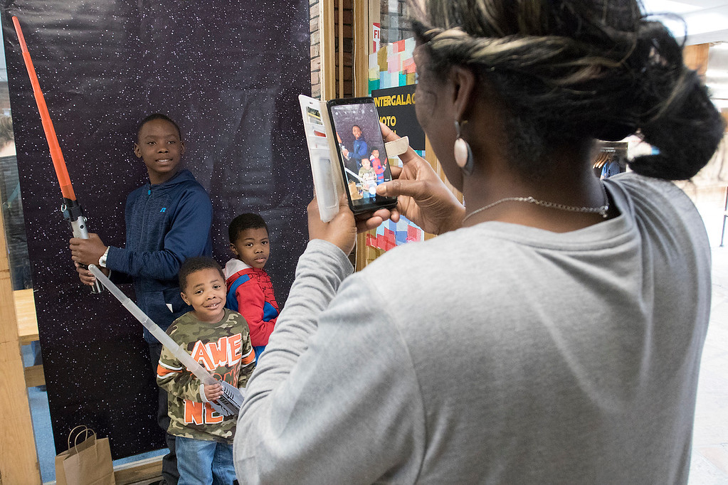 . The Fitchburg Public Library held a Star Wars day on Saturday, May 4, 2019. They had an Intergalactic Photo Booth at the event with some paper that had stars all over for you pose in front of for a picture. Zashanah Copeland takes a picute of her kids in the photo booth at the event. From left is J\'zziah Copeland, 11, Izrael Copeland, 3, and Azuri Copeland, 5. SENTINEL & ENTERPRISE/JOHN LOVE