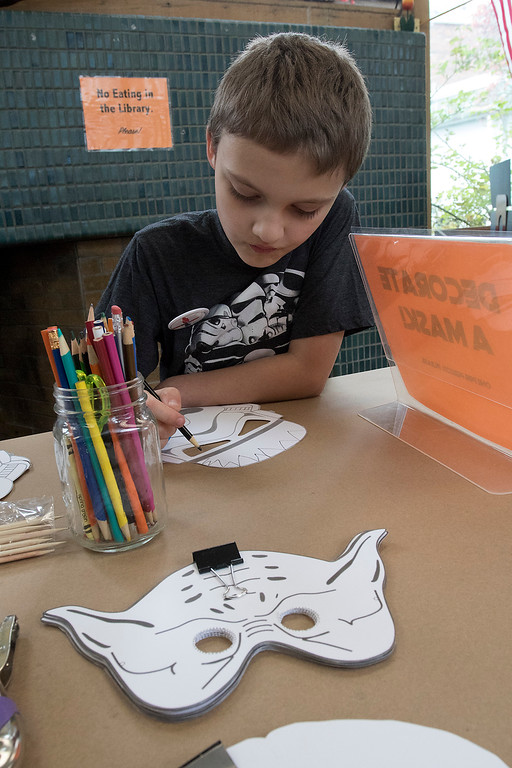 . The Fitchburg Public Library held a Star Wars day on Saturday, May 4, 2019. Decorating a stormtrooper mask during their event is Dennis LaClair, 9, of Fitchburg. SENTINEL & ENTERPRISE/JOHN LOVE