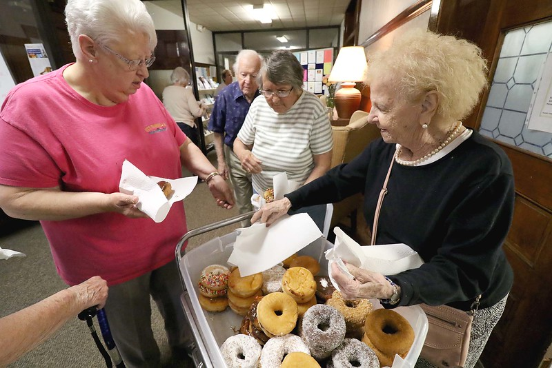 Josephine Cormier, on right, is a volunteer at the Fitchburg Senior Center. On Wednesday during a break in Bingo she got donuts for the players. SENTINEL & ENTERPRISE/JOHN LOVE