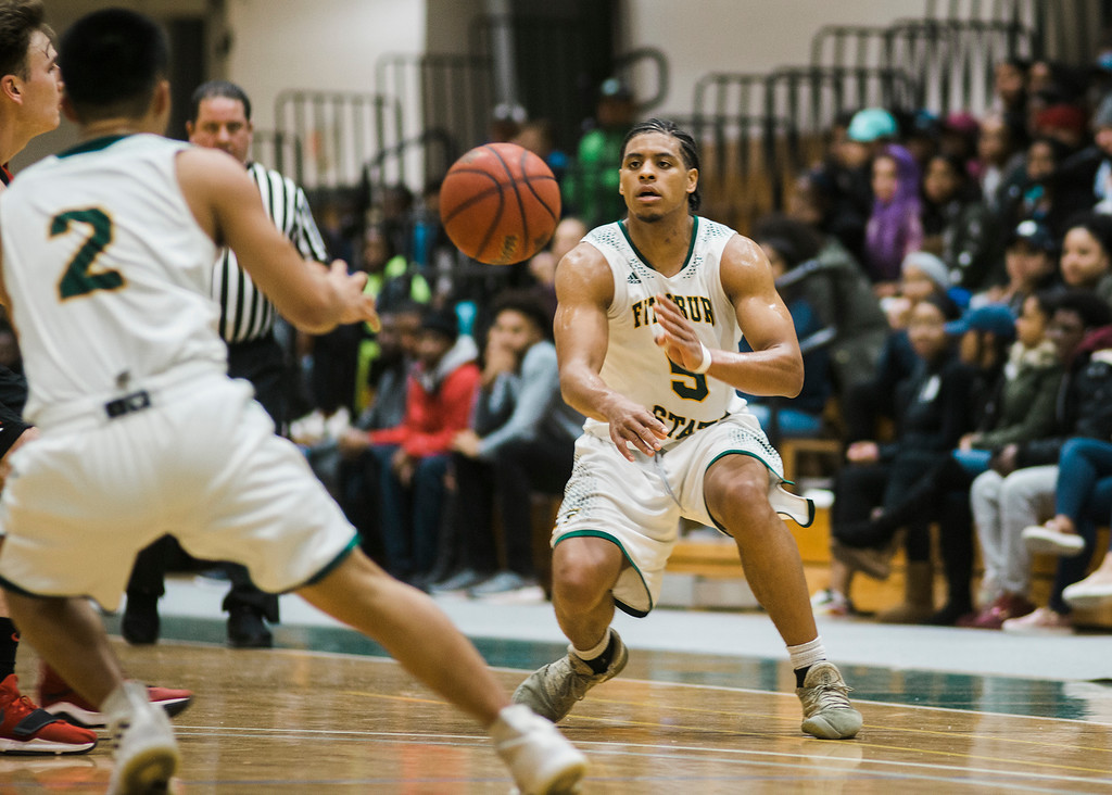 . Fitchburg State\'s #5 Jonathan Perez passes to #2 Brandon Guerrero during the game against Clark on Tuesday, December 5, 2017. SENTINEL & ENTERPRISE / Ashley Green