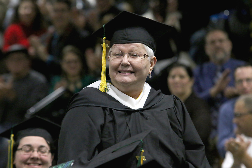 . Fitchburg State University graduate Claire Cabanillas, 76, stands as she is recognized by the University\'s Prsident Richard Lapidus as an outstanding student during his address at the Fitchburg State University 121 Annual Commencement on Friday December 22, 2017. SENTINEL & ENTERPRISE/JOHN LOVE