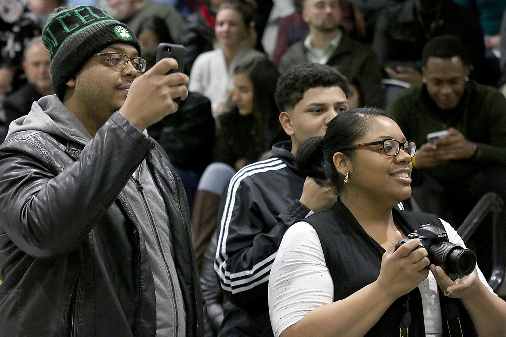 . Christopher Bryant and Tenishia Mulbah of Worcester take pictures of their sister as she graduates at the Fitchburg State University 121 Annual Commencement on Friday December 22, 2017. SENTINEL & ENTERPRISE/JOHN LOVE