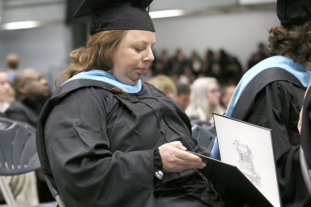. Courtney Bell of Leominster looks at her diploma at the Fitchburg State University 121 Annual Commencement on Friday December 22, 2017. SENTINEL & ENTERPRISE/JOHN LOVE