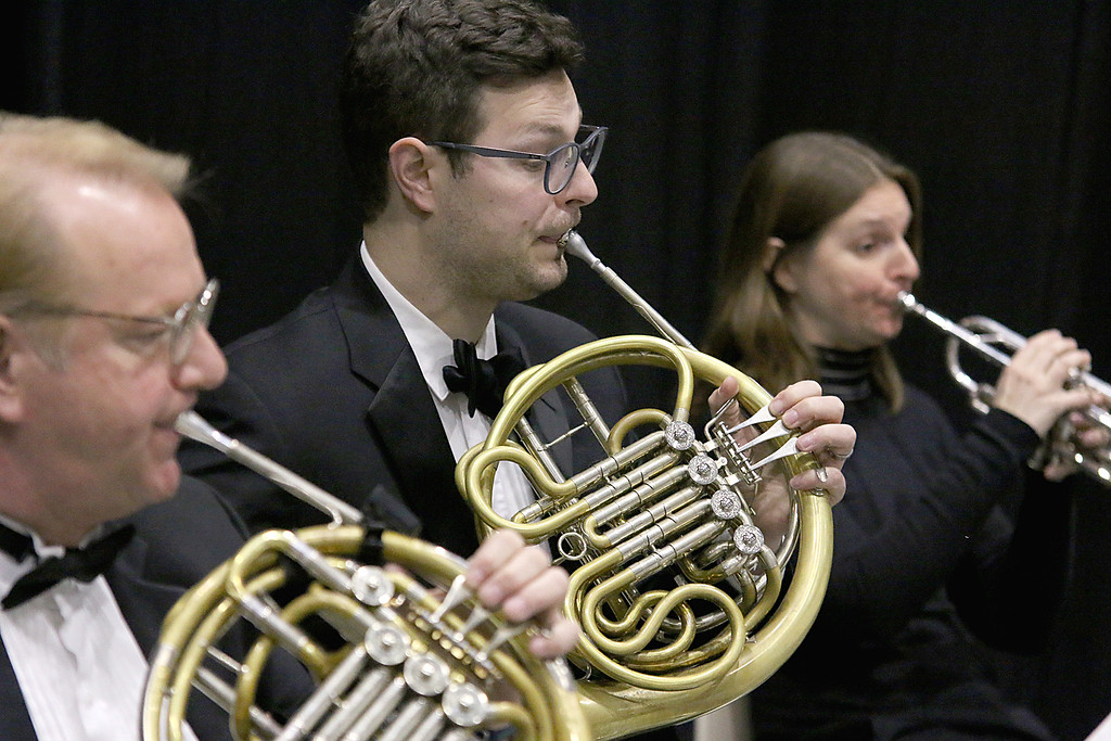 . Josh Michal, center, plays the French horn with the Innovata Brass at the Fitchburg State University 121 Annual Commencement on Friday December 22, 2017. SENTINEL & ENTERPRISE/JOHN LOVE