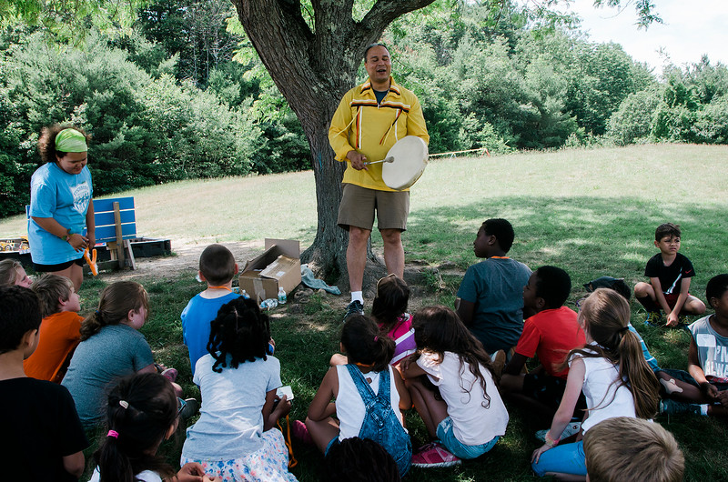 Native American storyteller Larry Spotted Crow Mann leads a presentation to students at Fitchburg Public Schools' Journeys Summer Camp to celebrate the opening of camp on Thursday, July 6, 2017. Mann is a member of the Nipmuc Tribe of Central Mass. and is a writer, poet, cultural educator, tribal drummer, dancer and traditional storyteller. SENTINEL & ENTERPRISE / Ashley Green