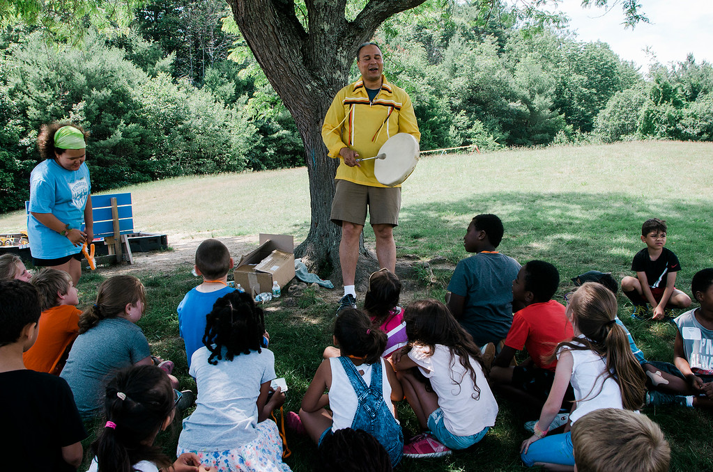 . Native American storyteller Larry Spotted Crow Mann leads a presentation to students at Fitchburg Public Schools� Journeys Summer Camp to celebrate the opening of camp on Thursday, July 6, 2017. Mann is a member of the Nipmuc Tribe of Central Mass. and is a writer, poet, cultural educator, tribal drummer, dancer and traditional storyteller. SENTINEL & ENTERPRISE / Ashley Green
