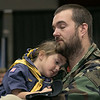 The City of Fitchburg held a Veterans Day ceremony at the Fitchburg Senior Center on Monday, Nov. 11, 2019. Army veteran Kevin Beaudry holds his daughter Jayne Beaudry, 5, in her Cub Scout uniform as they listen to the International Veteran's Chorus at the program. SENTINEL & ENTERPRISE/JOHN LOVE
