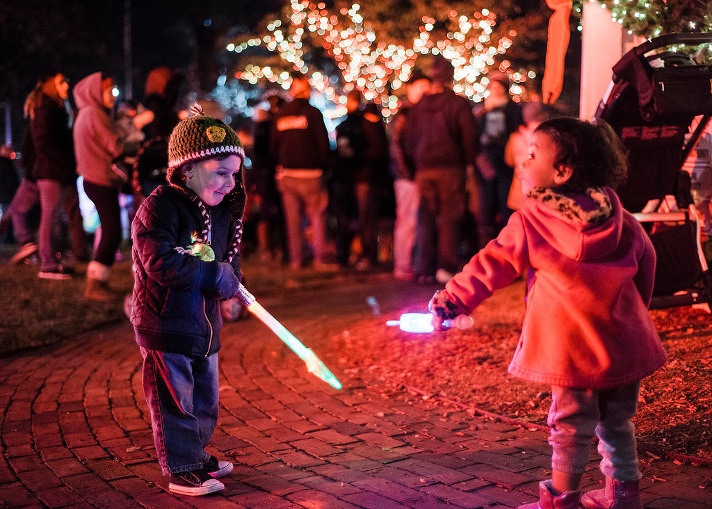 . Kellen Mallard and Catalena Forest play with lighted wands on the Upper Common during the annual tree lighting in Fitchburg on Saturday, December 2, 2017. SENTINEL & ENTERPRISE / Ashley Green