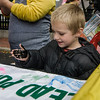 Xzavien Valle, 5, makes a handprint on a banner during trick-or-treating in downtown Fitchburg on Saturday afternoon. SENTINEL & ENTERPRISE / Ashley Green