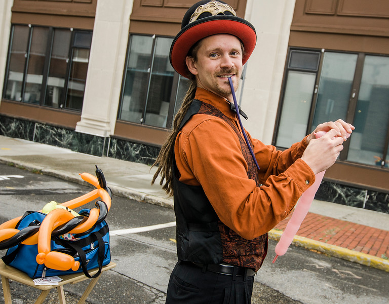 Maurice Eighme, of Circus Dynamics, blows up balloon animals during trick-or-treating in downtown Fitchburg on Saturday afternoon. SENTINEL & ENTERPRISE / Ashley Green