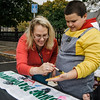 Jenna David paints the hand of Taiven Valle, 12, before he makes a handprint on a banner during trick-or-treating in downtown Fitchburg on Saturday afternoon. SENTINEL & ENTERPRISE / Ashley Green