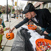 AJ Tourigney hands out candy to Eleuterio Silva, 5,  during trick-or-treating in downtown Fitchburg on Saturday afternoon. SENTINEL & ENTERPRISE / Ashley Green