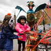 Violet, 5, and Evelyn Roland, 7, work on artwork with Jerry Beck of the Revolving Museum on Main Street during trick-or-treating in downtown Fitchburg. SENTINEL & ENTERPRISE / Ashley Green