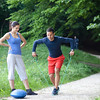 Personal trainer demonstrating a shoulder exercise using resistance band. Selective focus.