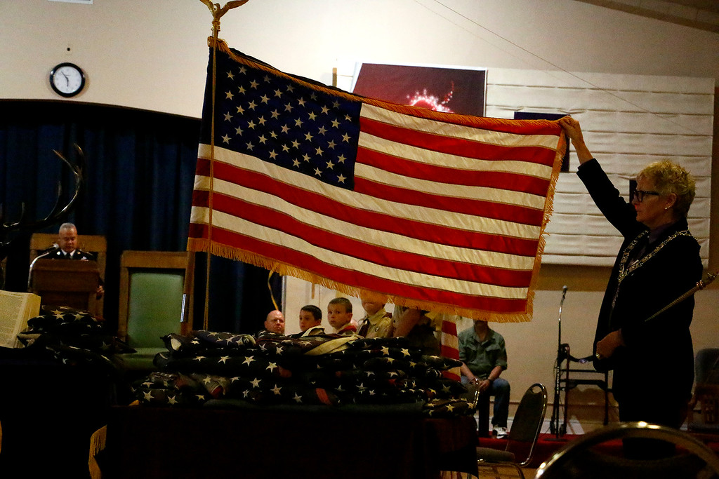 . Carole Anderson, left displays the flag over boy scout troop 314 as Sergeant Major Harold Johnson, a retired U.S. Army man, left, gives the history of the flag at the Elks Lodge, Wednesday evening, June 14, 2017. The Elks provided a ceremony on Flag day to respectfully retire tattered flags. (Michelle Risinger/ Loveland Reporter-Herald)