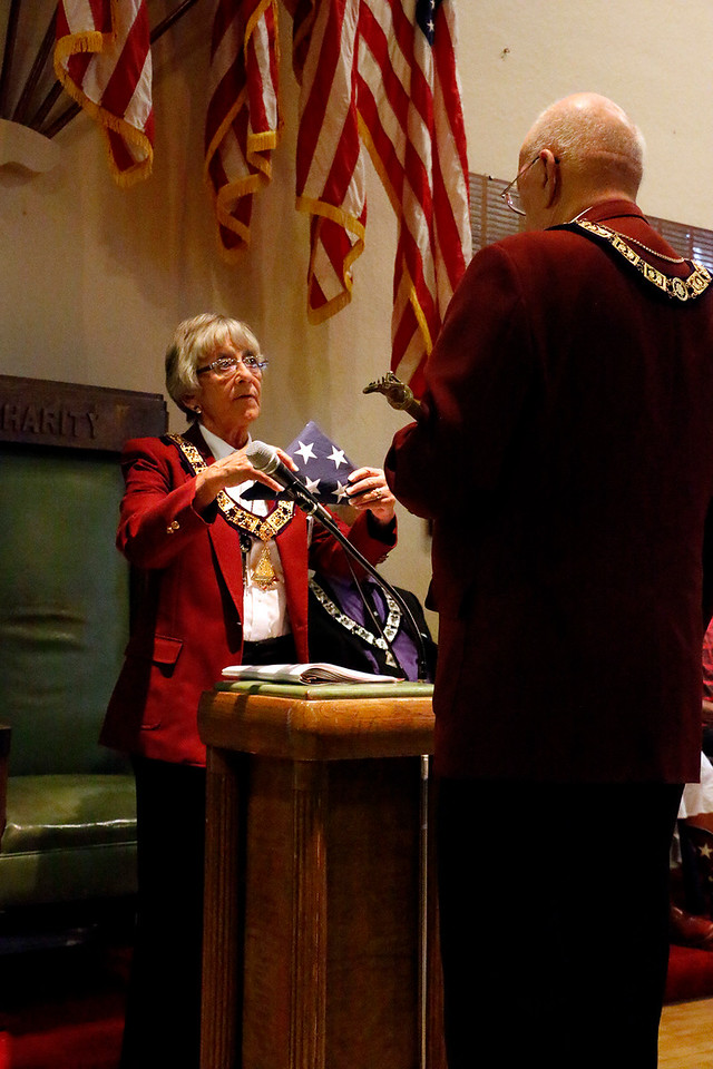 Shirley Brunelli, left, hands Dennis Epp, right, a retired service flag at the Flag Day ceremony held at the Elks Lodge 1051 in Loveland Wednesday, June 14, 2017. (Michelle Risinger/ Loveland Reporter-Herald)