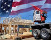 Construction crane setting house roof truss building America USA flag